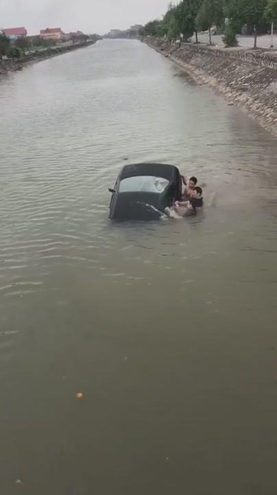 Đoạn video clip ghi lại cảnh người dân cứu tài xế khỏi cabin chiếc xe ô tô đang chìm (nguồn: Facebook)